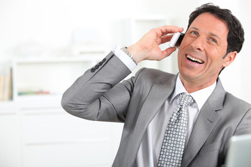 mature man wearing grey suit with tie is laughing