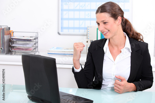 woman punching the air in delight after looking at her laptop