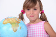Young girl with a large globe showing Africa