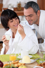 a woman giving a teaspoonful of yoghurt to his husband