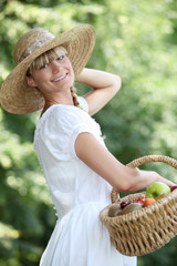 Carefree woman with a straw hat and wicker basket full of fruit