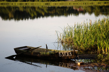 boat on the shore of a picturesque lake in the evening