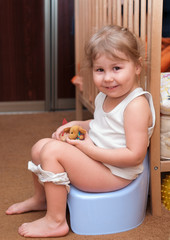 Little girl sitting on a chamber pot in the room