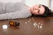 Teenage girl lying on floor after pills overdose