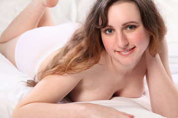 Beautiful happy young woman semi naked in bedroom