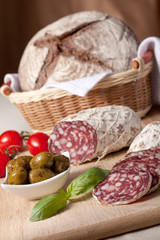 Slices salami on board, cherry tomatoes, olivas, bread in breadb