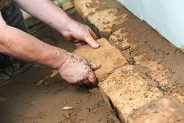 Mason hands at bricklaying works