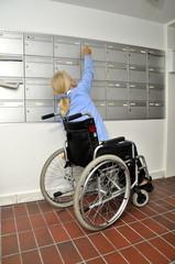 Behinderte Frau am Postkasten