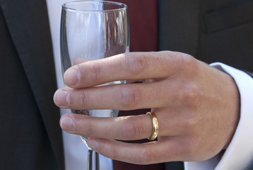 Hand holding glass with gold wedding ring