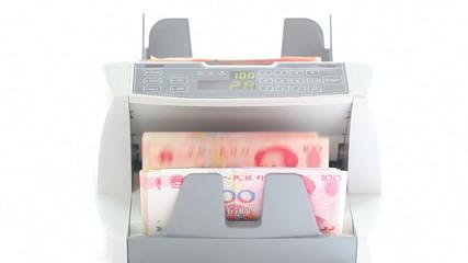 An electronic money counter processing yuan 100 bills.
