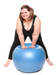 Happy overweight young woman with blue ball