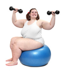 Shot of a overweight young woman with blue ball and dumbbells..