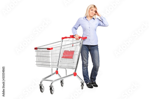 Bankrupt woman posing next to an empty shopping cart
