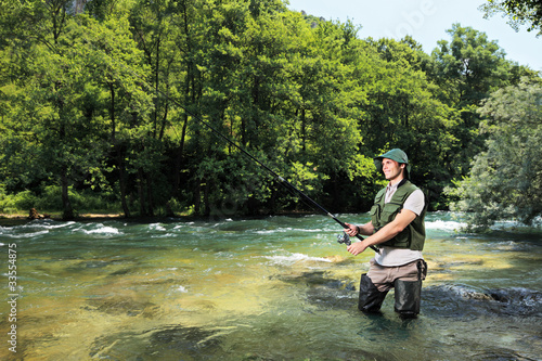 Fisherman fishing on a river with forest in the background