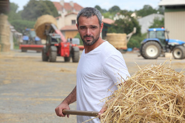 a farmer taking straw with a fork