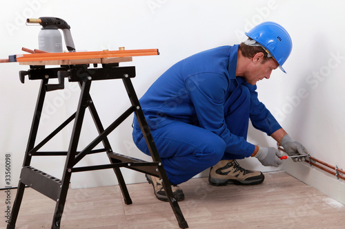 Laborer with screwdriver and blowtorch
