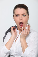 Young businesswoman shocked expression on face