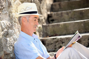 Senior man reading a magazine on some old stone steps