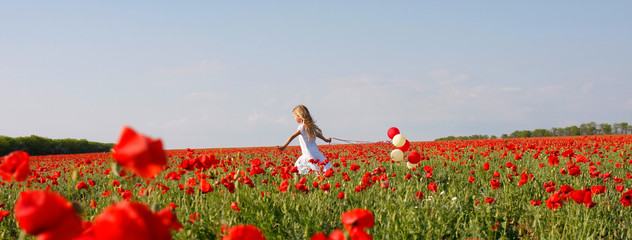 young girl running in poppy field