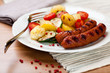 Grilled sausage with grilled vegetables on kitchen table