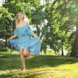 Young woman in blue dress jumping over green grass
