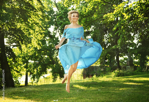Young charming laughing woman in beautiful dress jumps on meadow