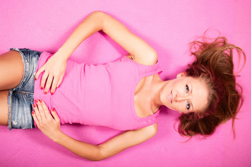 Portrait of sexy young woman lying in pink top on the floor