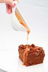 Sweet honey-cake with caramel sauce on a white plate