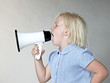 Little blond girl shouting loud through megaphone