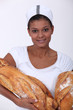 Female baker with large loaves of bread