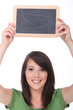 Young woman holding up a small blank blackboard