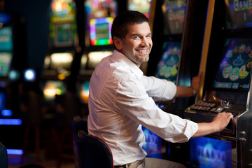 young man smiling next to the slot machine