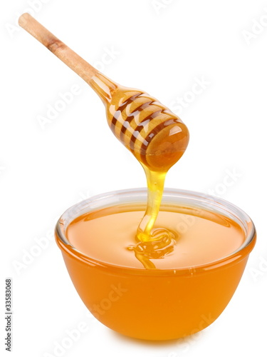 Bowl of honey and wooden stick.