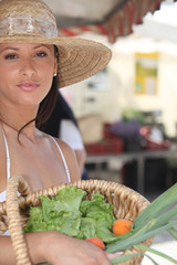 Summery woman in a straw hat holding a basket of market produce