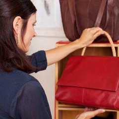 lächelnde frau kauft rote handtasche