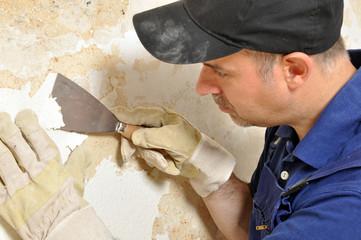 Handwerker beim Entfernen von Tapetenresten