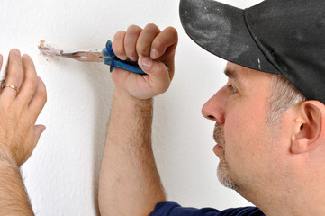 Handwerker zieht Dübel aus Wand
