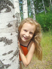 Little girl in birch grove