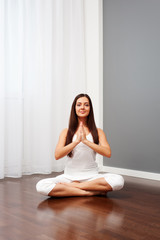 smiley woman doing yoga in room