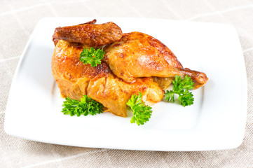 grilled chicken decorated with green parsley on white plate