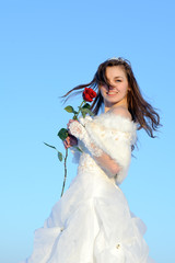 teenager posing in white wedding dress with rose