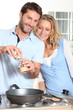 Couple using peppper grinder while cooking in the kitchen