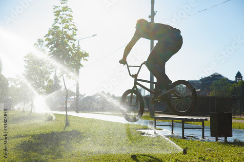 boy jumping over fountain on bmx