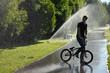boy with bmx stay on fountain splashes background