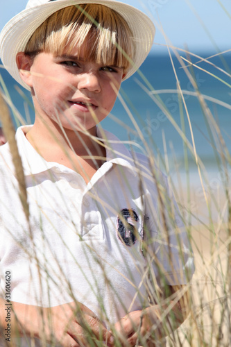 Little boy at the beach wearing hat
