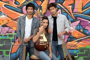 three guitarists behind a tagged wall