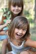 2 fillettes jouant dans la forêt (été, 5-6 ans)
