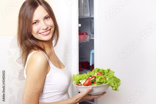 Young woman with healthy salad. background refrigerator