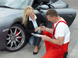 Mechanic giving car key to a business woman customer outdoors