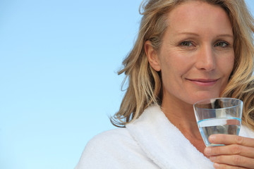 Attractive blonde haired woman drinking a glass of water